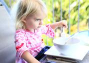 Little girl in adorable pink dress eating outside at summertime Stock Photos