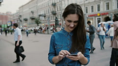 Modern technology. Beautiful brunette young woman in a denim dress using her Stock Footage