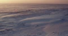 Pan towards setting sun over snow blown frozen tundra Stock Footage