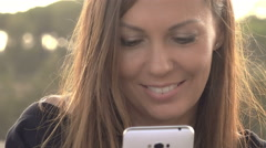 Happy smiling woman texting on a smartphone : front portrait handheld shooting Stock Footage