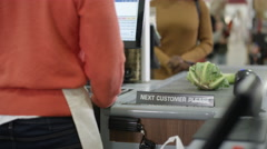 4K Friendly cashier taking payment from a customer at grocery store checkout Stock Footage