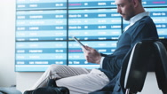 Man using Tablet while Waiting Boarding at Departure Lounge at the Airport. Stock Footage