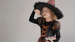 Girl wearing a black-orange dress and a big hat. Girl holds sweets in hands Stock Footage