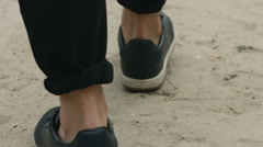 View from ground level with a man who tread on wearing sneakers, and passing Stock Footage