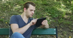 Young Man Sit Park Bench Using Digital Tablet Internet Surfing Social Networking Stock Footage