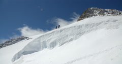 Two Mountaineers Crossing High Altitude Glacier in Windy Conditions Stock Footage