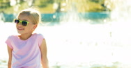 Portrait happy girl child 7-8 years relaxing near fountain at sunny day Stock Footage