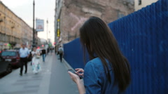 Young woman stands near a blue fence in the street. Lady uses a smartphone Stock Footage