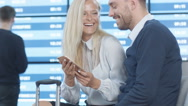 Man and Woman using Phone Together while Waiting Boarding at the Airport Stock Footage