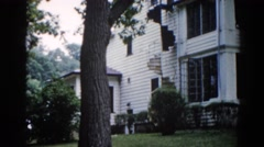 1962: an outdoor view of a beautiful two story house surrounded by trees Stock Footage