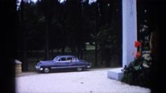 1962: the man watching an old lady from car when she is in the garden Stock Footage