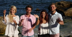 Happy Group of People Friends Looking Camera Smiling and Inviting Seaside Beach Stock Footage