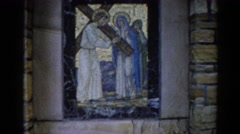 1962: a stained-glass window in a stone wall of christ carrying a cross Stock Footage