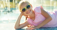 Portrait laughing child lying on fountain background at sunny day and looking Stock Footage
