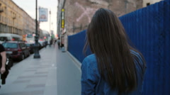 Lady walks in the street near blue fence. Backview of woman with long hair Stock Footage