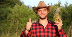 Happy Agriculturist Man Posing With Pineapple in Hand and Showing Thumb Up Sign Stock Footage