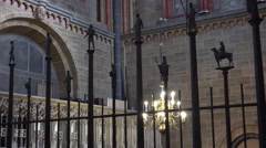 4k St. Peter's Cathedral indoor metal fencing with figures panning shot Stock Footage