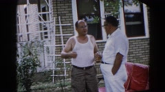 1962: two middle-age men stand in front of house and have a conversation in yard Stock Footage