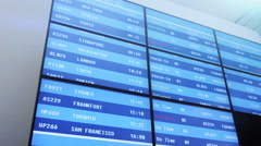 Business People Walking next to Information Board at the Airport. Stock Footage