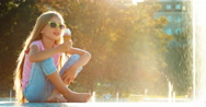 Girl 8 years old eating ice-cream on fountain background at sunny and hot day Stock Footage