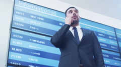 Businessman talking on Mobile Phone next to Information Board at the Airport. Stock Footage