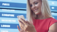 Attractive Smiling Blonde Woman Using Mobile Phone next to Information Board Stock Footage