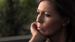 Beautiful woman feeling lonely and depressed sitting alone in a city park Stock Footage