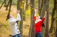 Couple on a walk in autumn park throwing leaves Stock Photos