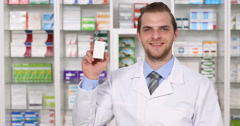 Smiling Pharmacy Employee Pharmacist Man Showing Drug Box Medicine Presentation Stock Footage