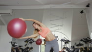 Woman doing a side stretching exercise using fitball in fitness studio Stock Footage
