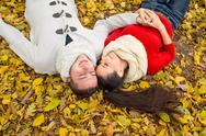 Beautiful couple in autumn park lying on the ground Stock Photos