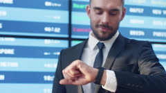 Businessman Looking Smart Watch while Standing next to Information Board Stock Footage