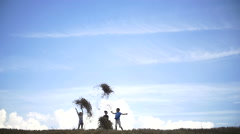 Children throw up hay in a field on a background of clouds Stock Footage