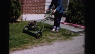1956: a lady in blue shirt and blue jeans trying to start a lawn mower in yard. Stock Footage
