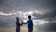 Boy giving a flower to girl on a background of clouds in the evening Stock Footage