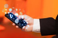 Business man holding smart phone with media icons Stock Photos