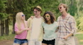 Two young happy couples embracing outdoors, singing and dancing in slow motion HD Footage