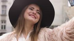 Smiling woman taking a self photo in urban street. Beautiful caucasian brunette Stock Footage