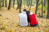 Beautiful couple in autumn park sitting on the ground Stock Photos