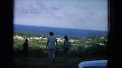 1964: strolling mother and daughters on a grassy hill HAWAII Stock Footage