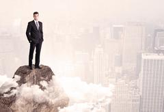 Happy businessman standing on stone top Stock Photos