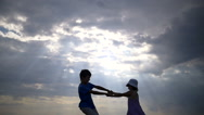 Boy with the girl circled holding hands on a background of clouds in the evening Stock Footage