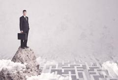 Businessman on cliff above labyrinth Stock Photos