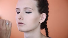 Makeup artist applying professional make up on the face of the beautiful young Stock Footage