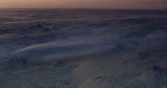 Orange glow of sunset over snow blowing across frozen tundra Stock Footage
