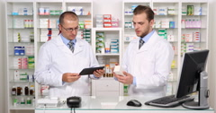 Pharmacist Men Discussing Medication on Internet Modern Pharmacy Staff Talking Stock Footage