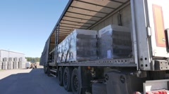 Forklift loads the truck with pallets of finished concrete products Stock Footage