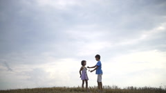 Boy giving a flower to fashionable girl on a background of sky. Love concept Stock Footage