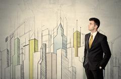 Businessman standing with drawn cityscape Stock Photos