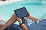 Man sitting by pool with a digital tablet Stock Photos